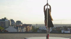 Fit attractive girl dancing near portable pole at summer day over the skyline - stock footage