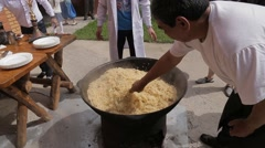 Cooking pilaf in a cauldron Stock Footage