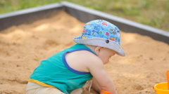 Baby boy digging in the sandbox. Smiles and touches the sand - stock footage