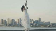 Fit attractive girl posing on the portable pole at summer day in wedding dress Stock Footage