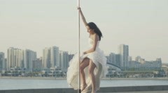 Fit attractive girl dancing on the portable pole at summer day in wedding dress Stock Footage