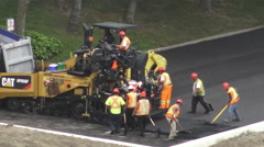 City workers paving the road on a rainy day - stock footage