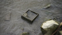 Discarded computer case in the side of a river Stock Footage