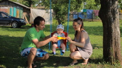 Father and mother playing with baby boy on a swing. The garden around the house - stock footage