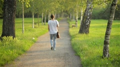 Beautiful young woman walking through the park, nice weather Stock Footage