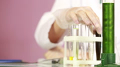 Female chemist comparing test tubes with chemicals. protective glasses Stock Footage