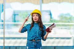 Woman builder taking notes at construction site - stock photo