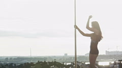 Sexy girl dancing on the portable pole at summer day over the skyline, slow Stock Footage