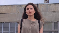 Sad Beautiful Girl Standing Against a Background of Industrial Ruined Buildings - stock footage