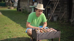 Man prepares meat on the fire. Twists meat over a fire in the garden Stock Footage