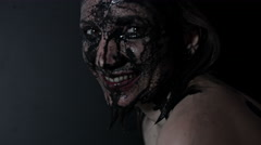 4k shoot of a horror Halloween model - Woman washing black mud and smiling Stock Footage