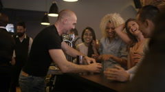 4K Friendly bar staff serving drinks & shots to party crowd in city bar Stock Footage