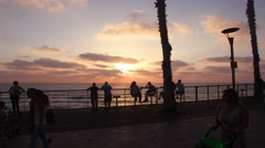 Silhouettes of people against the sunset and the sea. Time lapse. Stock Footage