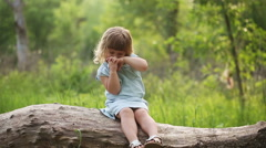 Little girl rubs her eyes outdoors Stock Footage