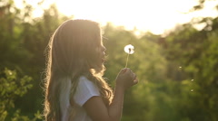 Little girl is blowing a dandelion - stock footage