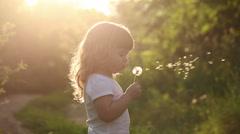 Cute little girl is blowing on dandelion Stock Footage