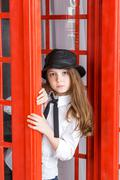 little girl looks out from a phone booth - stock photo
