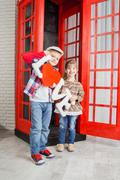 boy and girl in the phone booth - stock photo