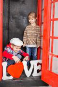 Boy and girl in the phone booth Stock Photos