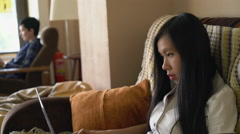 Two mixed race women sitting with modern device in modern loft Stock Footage