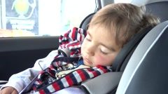 Child sleeps on car seat in the car Stock Footage