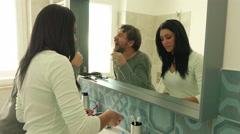 Happy people in bathroom in the morning washing teeth cutting beard - stock footage