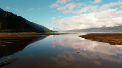 Aerial: Still lake water reflecting clouds grasses and mountains in Patagonia 2K Stock Footage