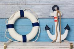 Anchor and life buoy on wood background blue-white Kuvituskuvat