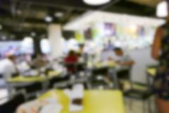 blurry defocused image of people eating food in food court - stock photo