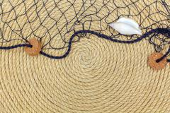 Seashell and marine network lie on background made of rope Stock Photos