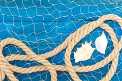 Marine network rope and shells on blue disks Stock Photos