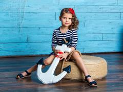 Child sitting and holding an anchor Stock Photos