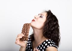 Beautiful young woman eating a chocolate bar, wears a dress with polka dots - stock photo