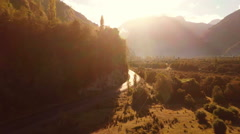 Aerial: Road going through mountain valley golden sunrise slow tracking 2K Stock Footage