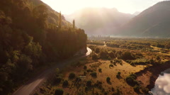 Aerial: Mountain road through valley at sunrise with car pickup truck driving Stock Footage