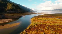 Aerial: Lake and river in patagonia mountains camera lift over reflective water Stock Footage