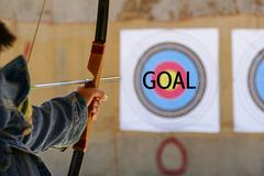 archer is aiming the archery at the target - stock photo