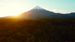 Volcano aerial tracking shot away over forrest with sun setting in Patagonia Stock Footage