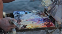 An artist's palette with Oil paint close up. Evening summer sea Stock Footage