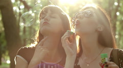 Beautiful girls having fun making funny selfie and blowing soap bubbles - stock footage