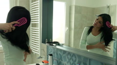 Happy woman in front of mirror singing while brushing long black hair Stock Footage
