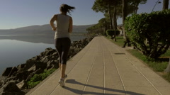Happy woman jogging in front of lake slow motion from back Stock Footage