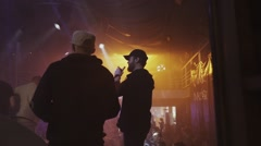 Man exhale clouds of steam from electronic cigarette on stage of nightclub - stock footage