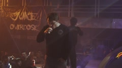 Boys exhale steam from electronic cigarette on stage in nightclub. Searchlights - stock footage