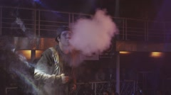Boys exhale steam from electronic cigarette on stage of nightclub. Contest - stock footage