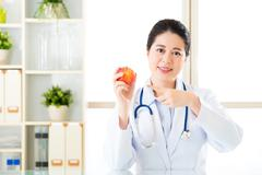 Young asian nutritionist recommend eating apple - stock photo
