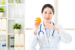 Young asian nutritionist recommend eating orange - stock photo