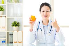 Young asian nutritionist recommend eating orange and thumbs up - stock photo