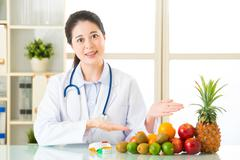 Young asian nutritionist recommend eating fruits - stock photo