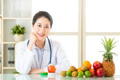 Young asian nutritionist recommend eating fruits Stock Photos